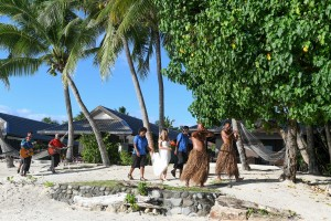 The bride walks down the aisle with a traditional Fiji procession