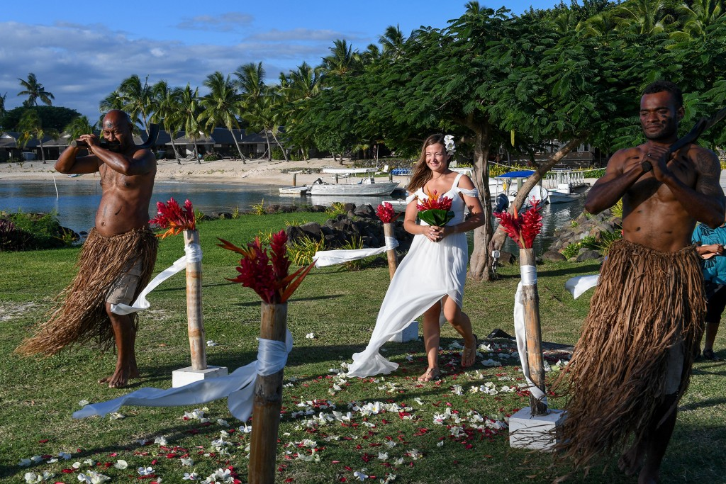 The stunning bride walks down the aisle escorted by traditional Fiji dancers