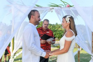 The bride and groom hold hands as they share vows at the altar