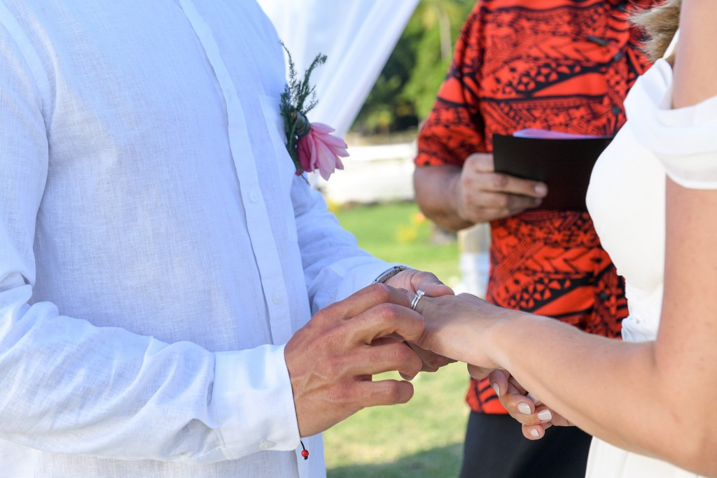 The grooms slips the ring on his bride's finger