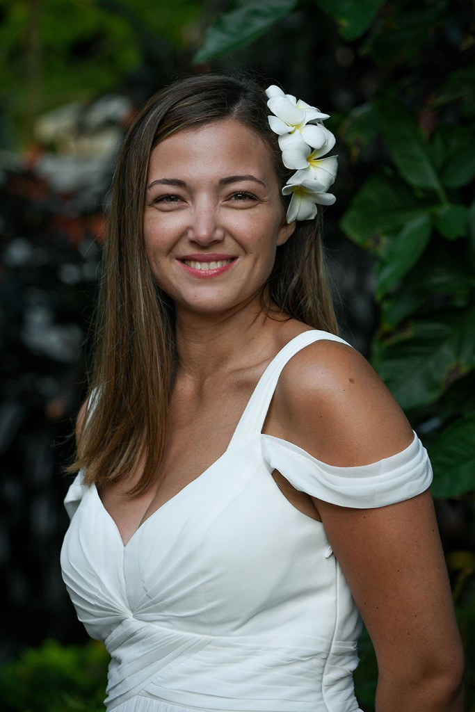 A portrait of the stunning bride with a white frangipani flower tucked in her hair