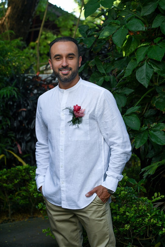 The groom poses in white and khaki with a ginger flower boutonniere