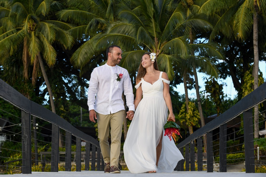 The couple strolls hand in hand on the Fiji dock against palm trees