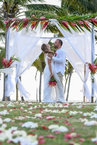 The married couple laugh under the arch altar made of ginger flowers and rose petals on the aisle