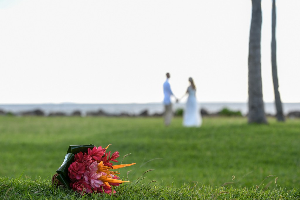 The married couple hold hands in the background with a ginger flower bouquet in the foreground