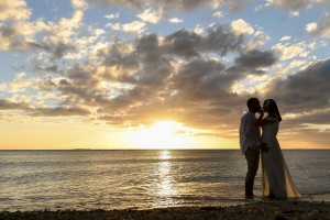 The married couple embrace against the golden Fiji sunset