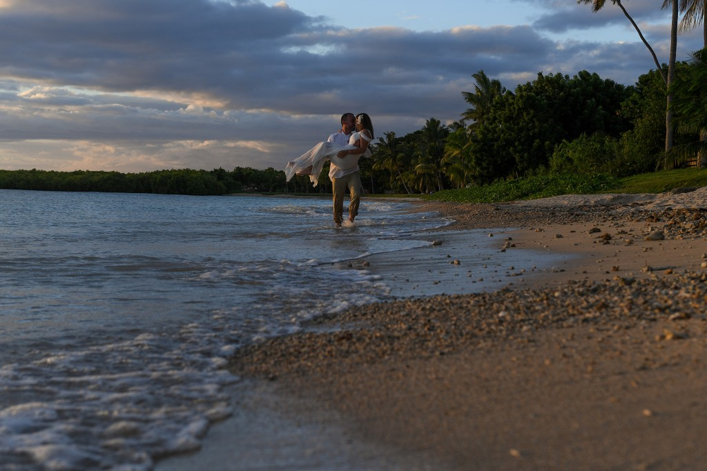 The groom carries his bride as he wades in the ocean at sunset