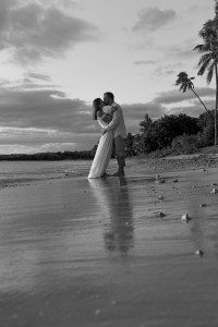 A monochrome image of the loving couple kissing in the sunset