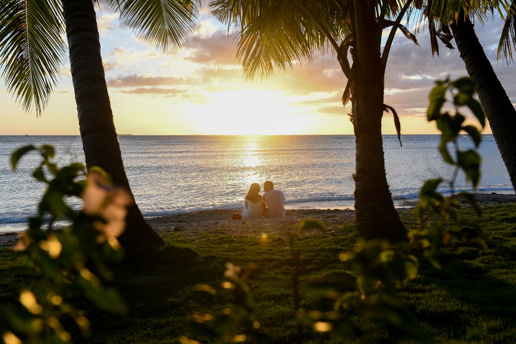 The loving couple sit between palm trees and stare into the golden Fiji sunset
