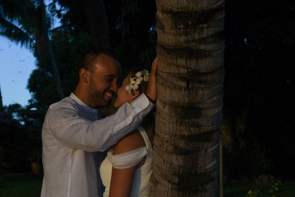 The couple share an intimate moment against a palm tree