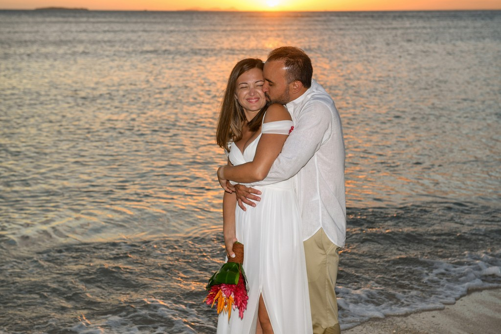 The couple share an intimate kiss in the ocean against the golden Fiji sunset