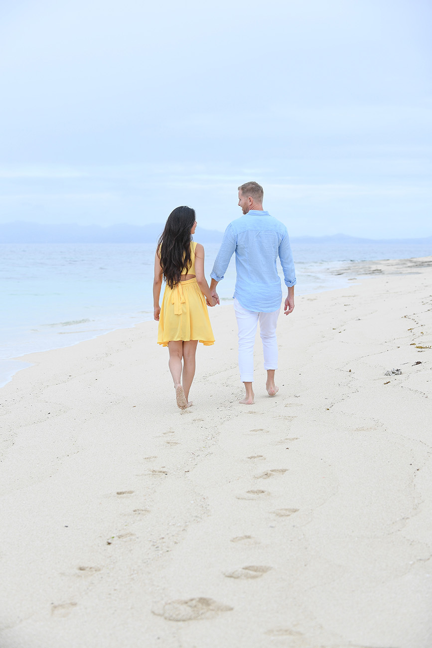 The couple strolls hand in hand against baby blue sand