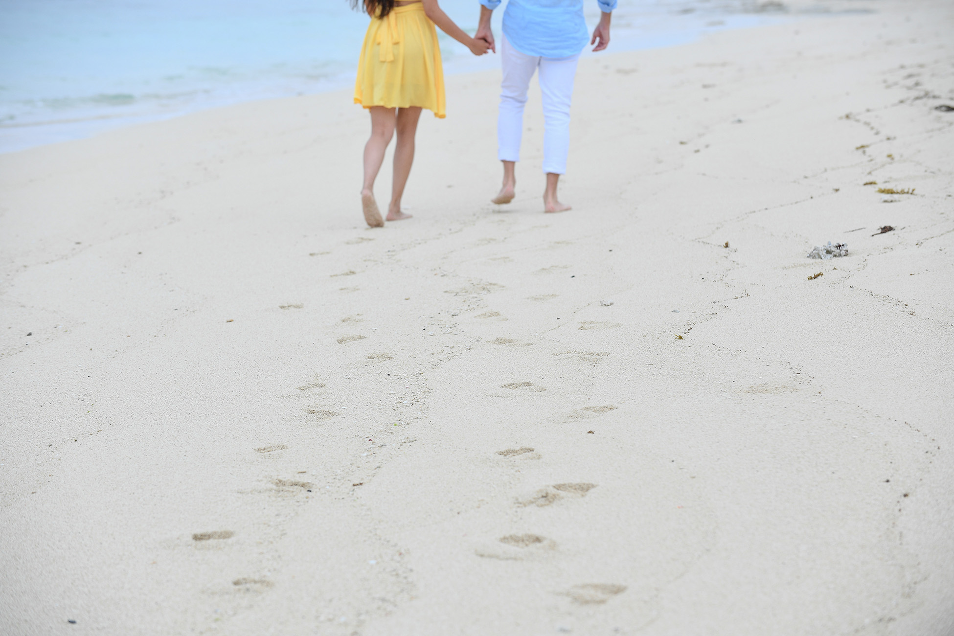 The newly engaged couple leave footprints on the beige Mamanunca beach of Fiji