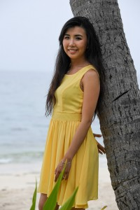 The bride-to-be dressed in a bumbleebee yellow dress leans against a palm tree