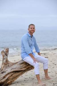 The groom to be in a denim shirt on the beach