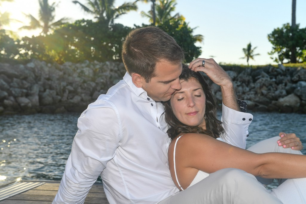 The bride and groom lovingly embrace in the Fijian sunset