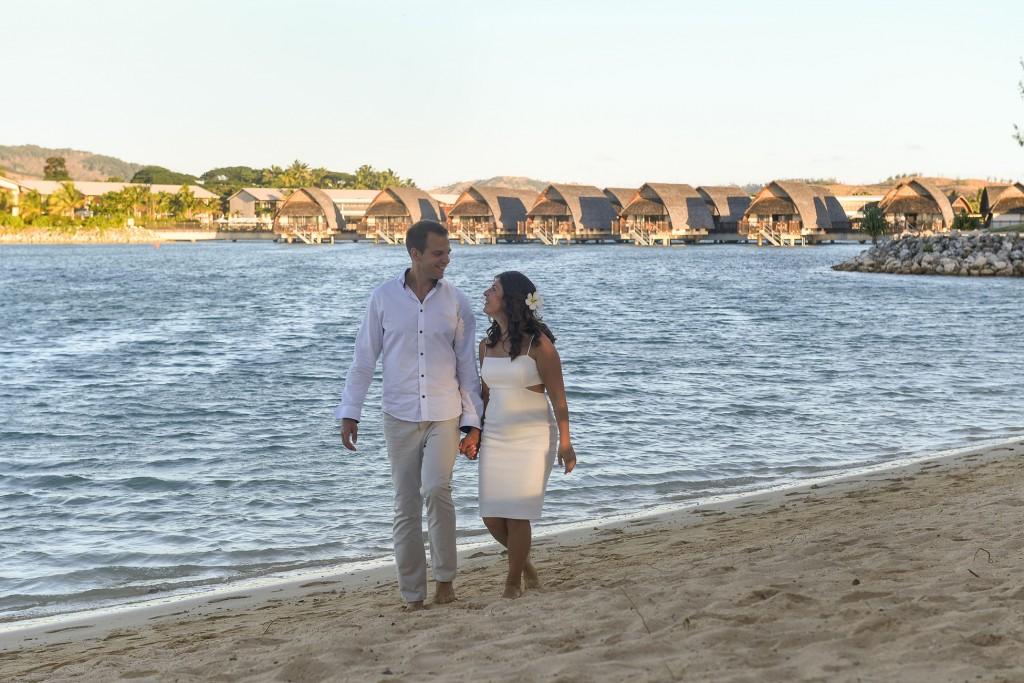 The couple strolls hand in hand along the Fiji beach at sunset