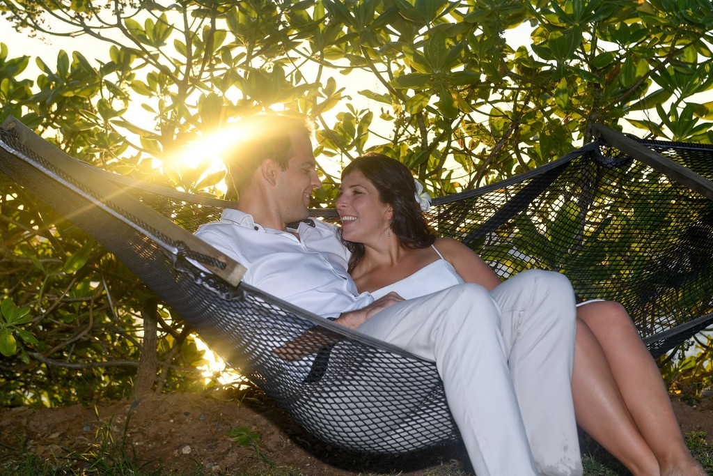 The couple cuddles on a hammock with the sunset peering through the trees