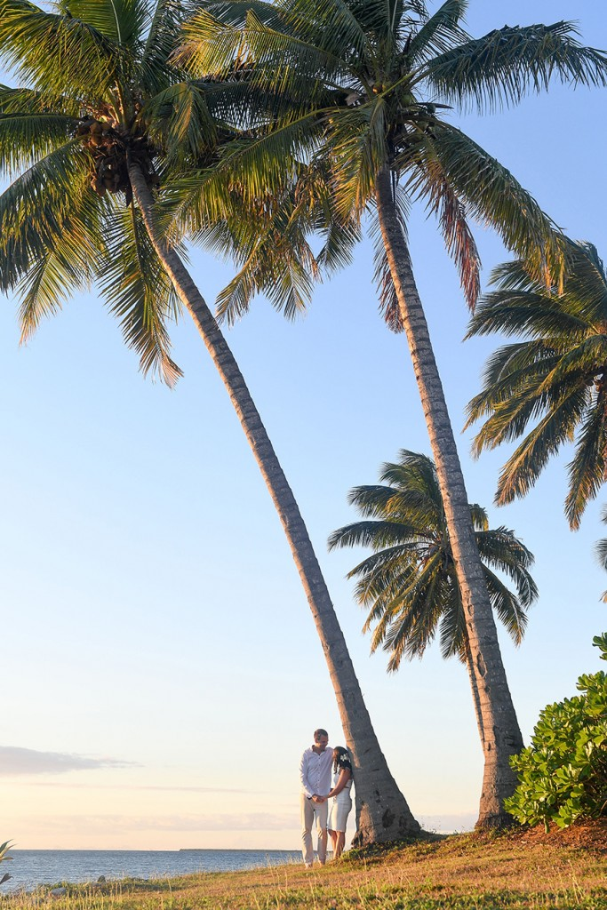 The couple cosies up against gigantic palm trees on the beach