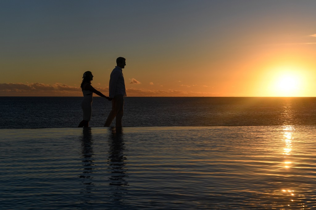 A silhouette of the couple strolling along the ocean at sunset