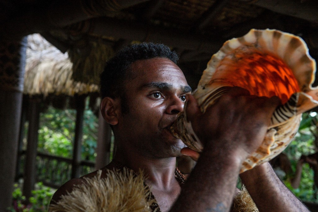 A man blows on a traditional Fiji shell horn