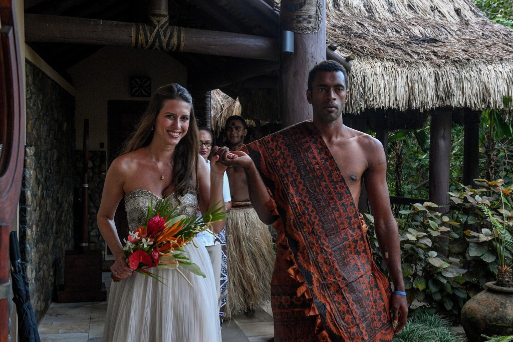 The stunning bride is escorted by a traditional Fiji warrior