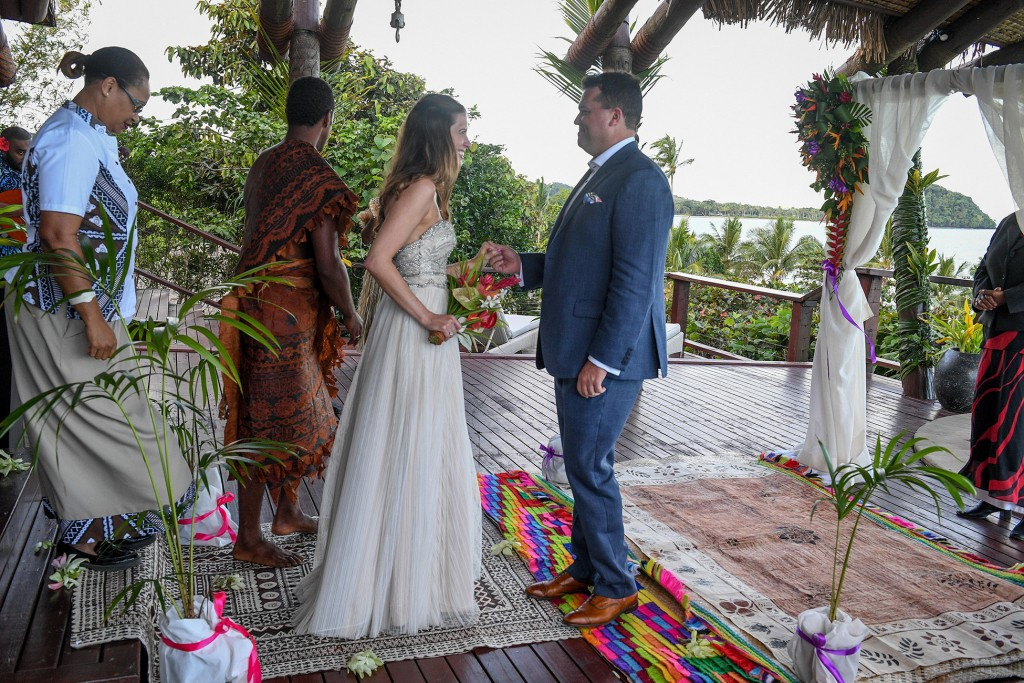 The groom receives the bride on the colourful Fiji altar