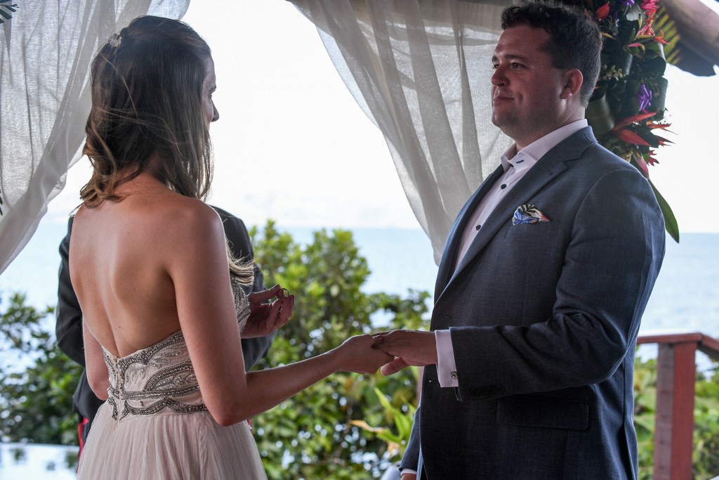 The bride says her vows before she slips the groom's ring on his finger