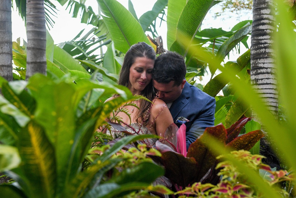 The groom gently kisses his bride on the shoulder in the heart of green Fiji