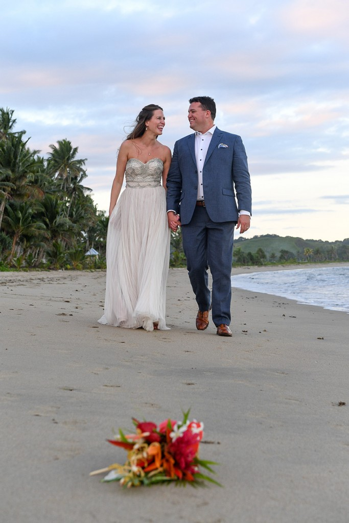 The newly weds share laughter while strolling on the beach
