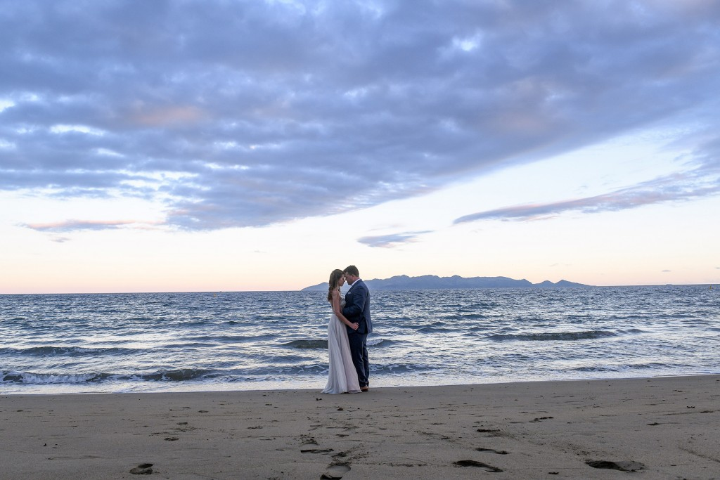 The couple share an intimate moment against the fading Fiji sunset
