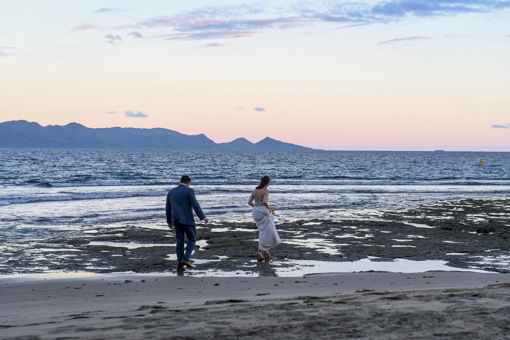 The couple walks on the wet beach at sunset