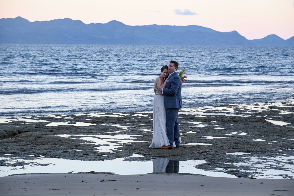 The couple embraces on the black sand beach