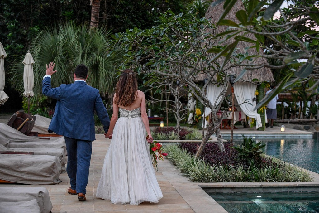 The newly weds wave as they stroll beside their personal pool