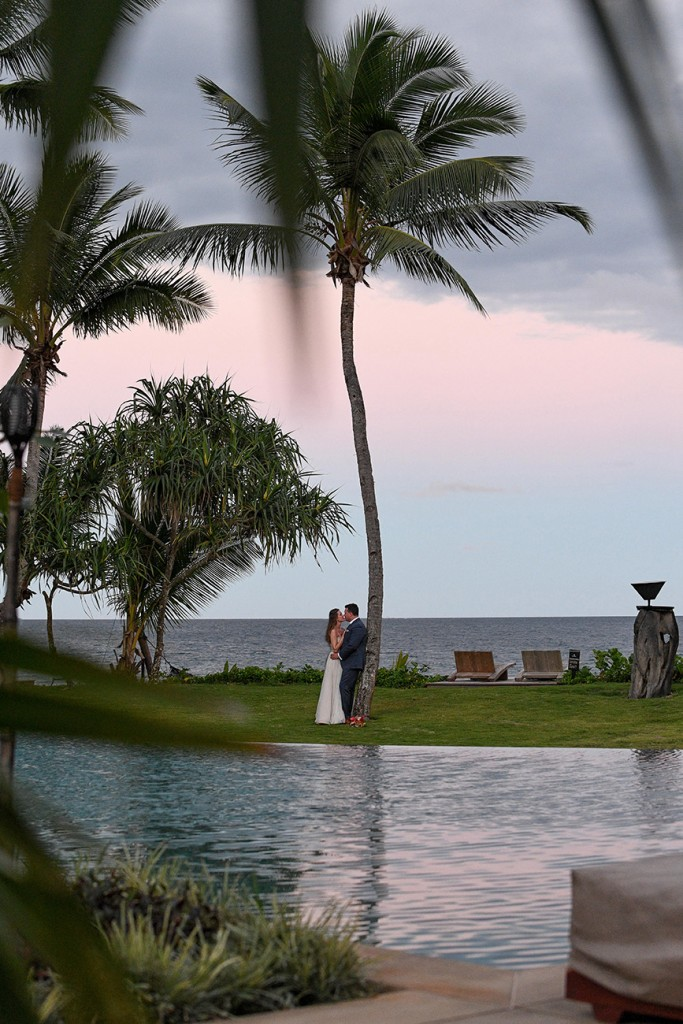 The newly weds kiss against towering palm trees at Nanuku Island Fiji