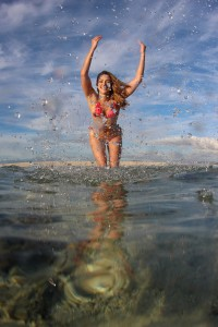 The model throws water at the camera lens