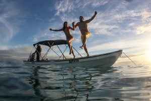 The couple hold hands as they leap off the boat into the Pacific