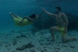 The couple high fives underwater