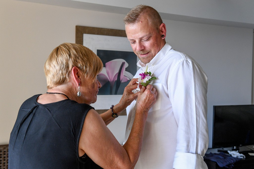 The mother of the groom tucks a tropical flower boutonniere on the groom
