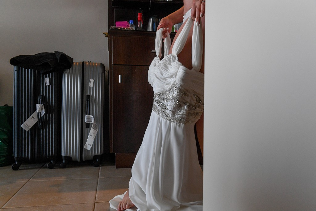 The bride steps into her stunning V neck wedding gown