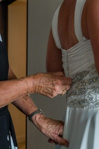 The bride is zipped into her brilliant whit wedding gown