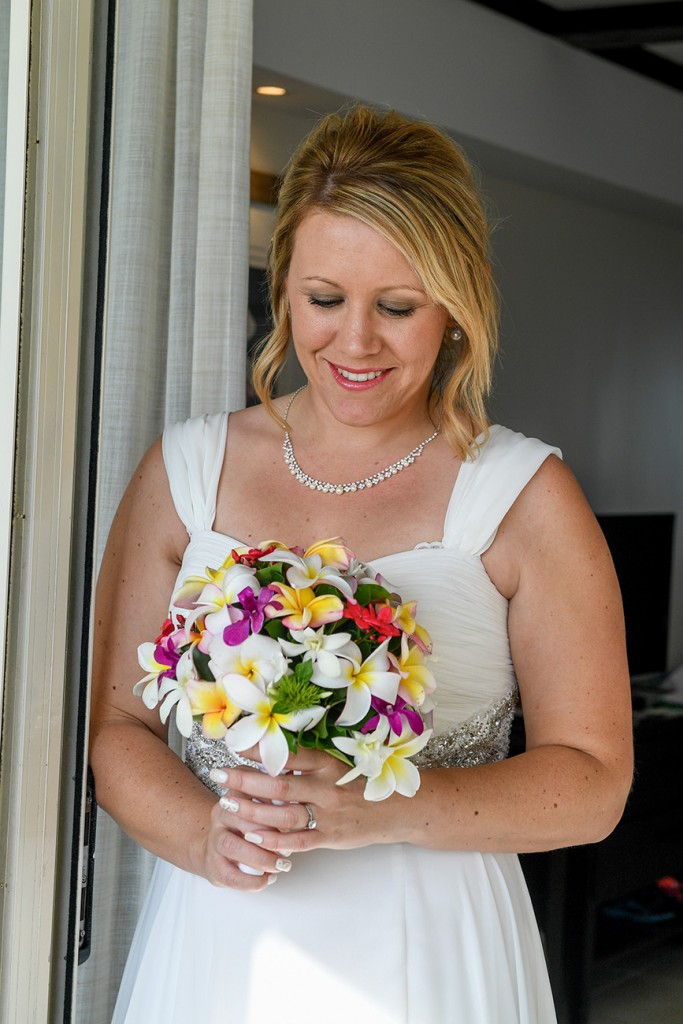 The bride poses with her colourful tropical flower bouquet