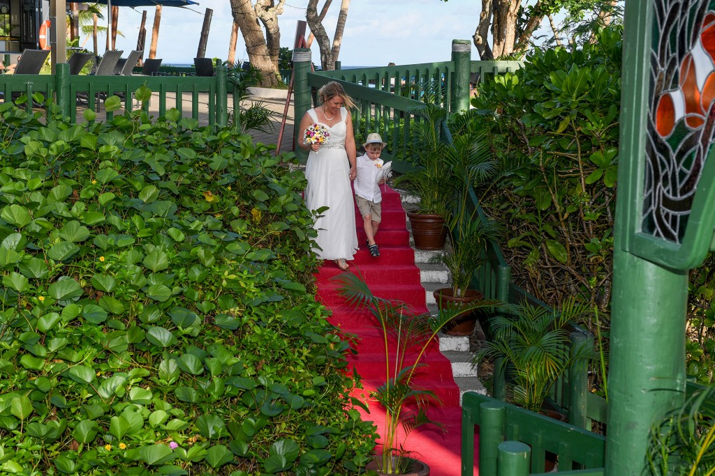 The bride walks down a red carpet aisle with the her son