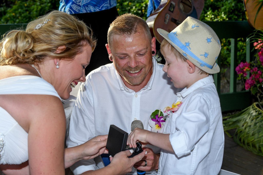 The bride and groom smile with their son who presents their rings