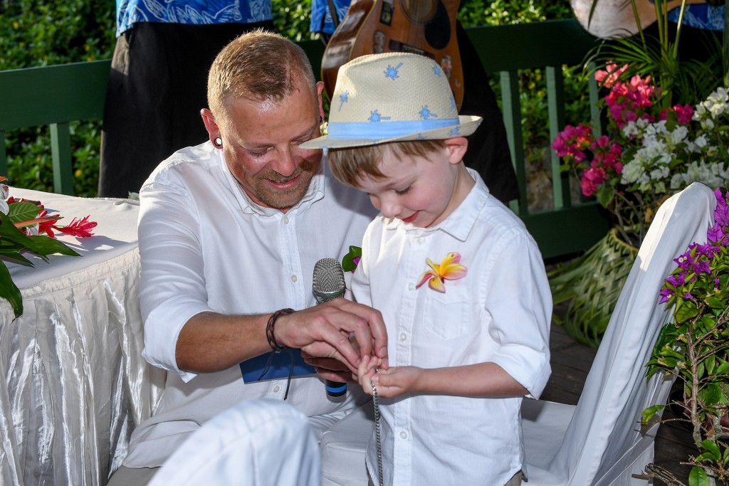 The groom helps his son unstring the rings