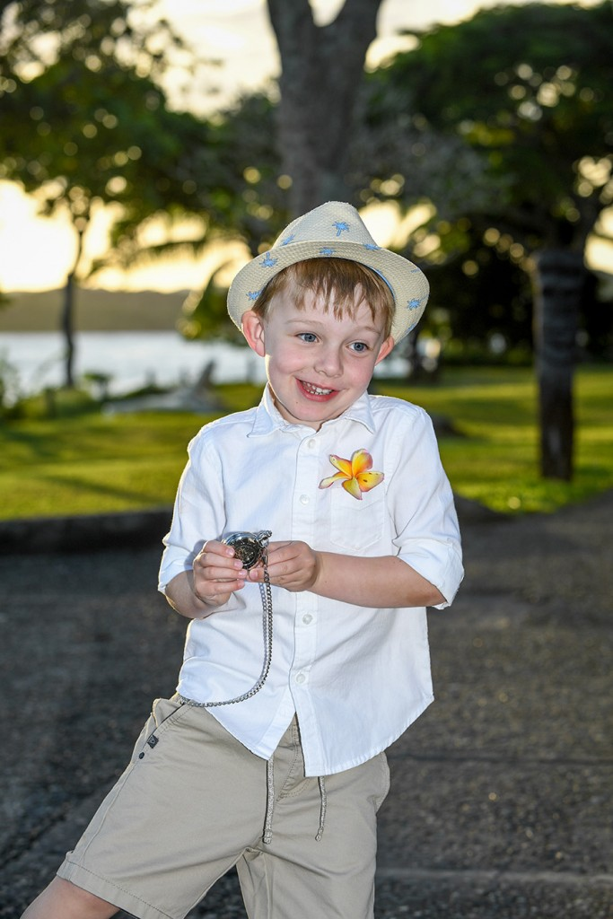 The newly wed couple's son plays with a pocketwatch at the beach