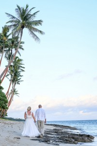 The newly weds stroll on the beach under palm trees in Shangri La Fiji