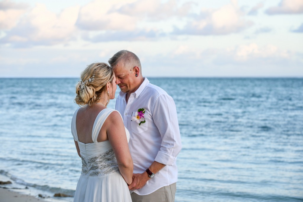 The newly weds share an intimate moment beside the ocean