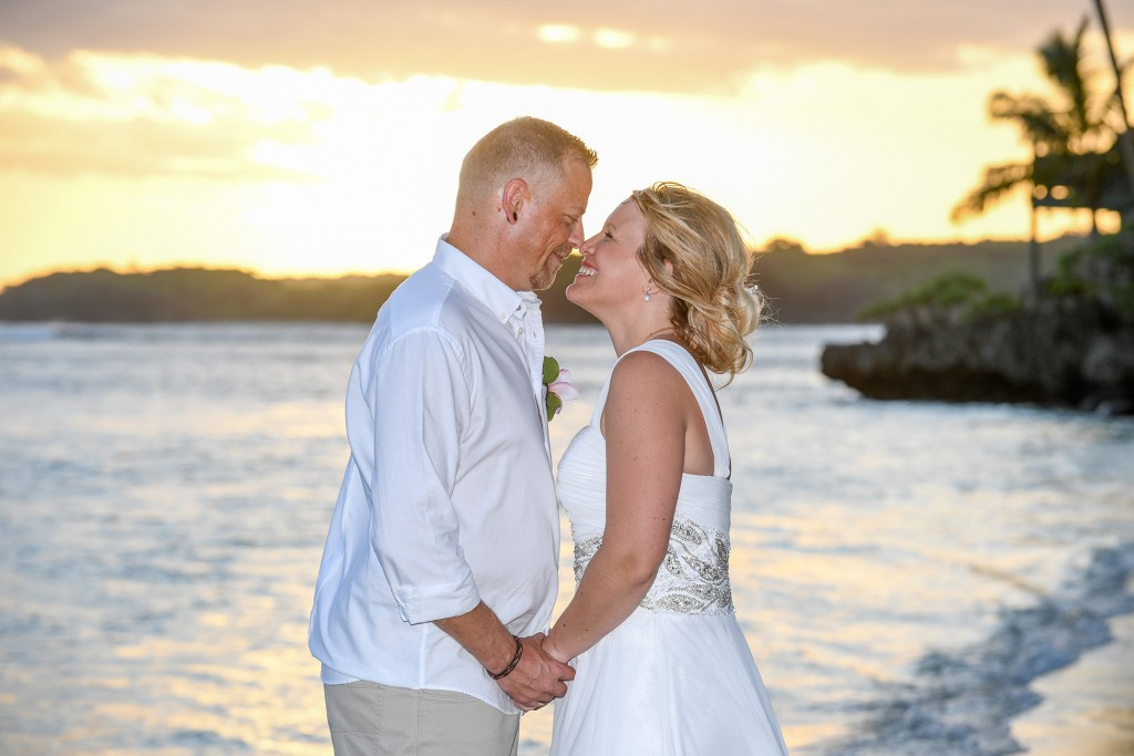 The newly weds share an intimate moment against a fiery Fiji sunset