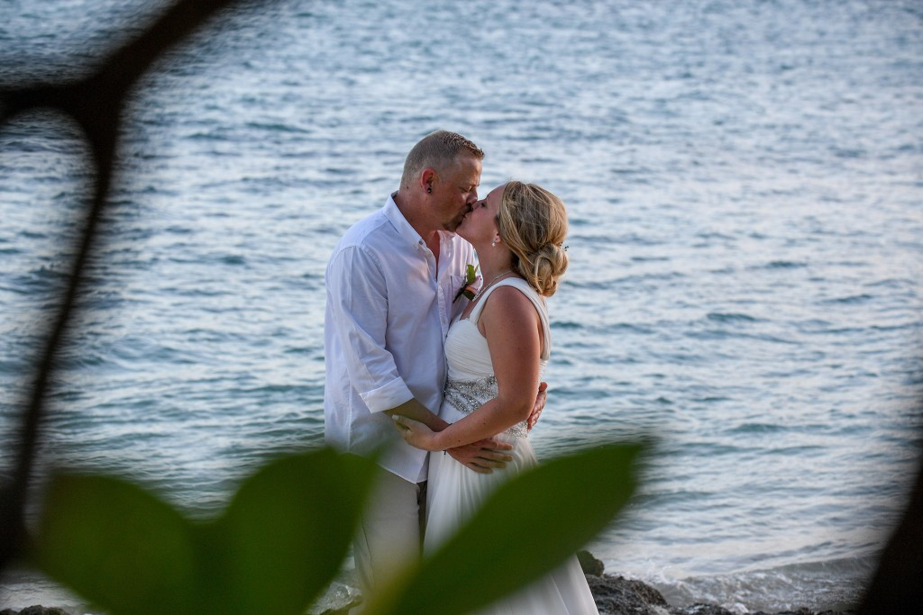 The couple passionately kisses on the shores of the Pacific Ocean at sunset